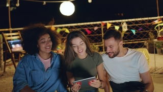 Diverse Group Of Young Hipsters Friends On Rooftop Looking At A Tablet Smiling And Sharing Funny Internet Videos Looking At A Project Together Teamwork Fun Time With Technology At Party 3g 4g 5g Futur