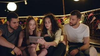Young Friendly People At Celebration Rooftop Party Looking At A Tablet Smiling And Sharing Funny Internet Videos Looking At A Project Together Teamwork Fun Time With Technology At Party 3g 4g 5g Futur