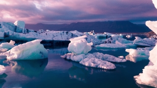 Epic Aerial Flyover Over Iceberg Pieces Melting In A Beautiful Ice Lake Purple Sunset Climate Change Spirituality