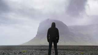 Epic Aerial Flight Away Man Standing in Front of Nordic Mountain Landscape Majestic Scale Facing Problems Concept Loneliness Seclussion Depression