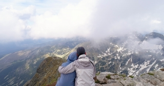 Aerial Flight Over Couple Sitting in Cliff Edge Alpine Mountain Epic Alpine Mountain Range Hiking And Travel Romantic Relationship Love Adventure