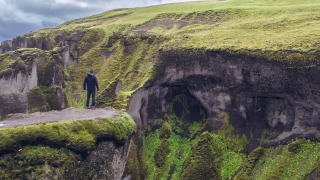 Aerial Flyover Around Man Standing at Iceland Mountain Landscape Canyon Freedom Inspiration Success Travel Adventure Concept