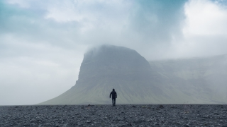 Aerial Flight Over Lonely Brave Man Figure Walking to Nordic Mountain Landscape Beautiful Fog Clouds Rain Loneliness Facing Challenge Bravery Concept