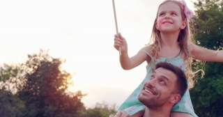 Young Father Carrying Child On Piggyback Ride Through Park At Sunset Smiling Enjoying Happiness Happy Family Time Concept Slow Motion Shot On Red Epic 8K