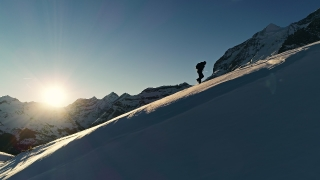 Winter Aerial Over Winter Extreme Sport Hiker Climbing Up To Mountain Top At Sunrise Golden Hour Swiss Alps Vacation Outdoor Adventure Happiness Achievement Concept