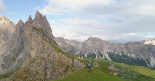 Adventurer Man Walking Through Alpine Peaks Scenery In The Mountains Peaceful Mountain Happiness Aerial Drone Flight