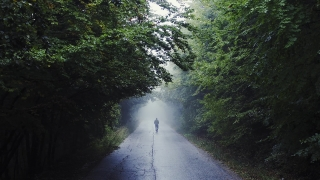 Lonely Hooded Man Walking Toward The Light During Rainy Day Youth Depression Backpacking Slow Motion Drone