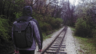 Lonely Hooded Man Walking Railroad On A Rainy Day Solitude Backpacking Slow Motion 4 K Raw