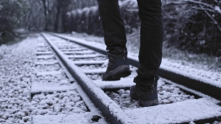 Tourist Walking On Deserted Snowy Railway Camera Tracking During Snow Storm Loneliness Social Restrictions Slow Motion 4k Hdr