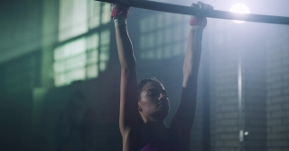 Young Adult Female Athlete Gymnast Doing Exercise On Pull Up Bar Sports Center Physical Strength Motivation Gymnastics Competitive Mindset Concept 4k