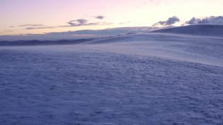 Aerial Shot Of Wind Blowing Winter Mountain Hills At Sunset Sunrise Colorful Purple Orange Sky Cold Weather Cinematic Flight 4k