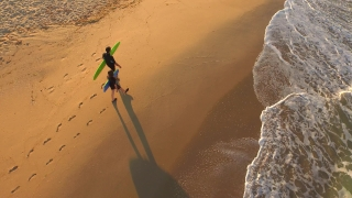 Man Woman Surfers Walking On Beach Looking For Waves Sunset Sand Ocean Aerial