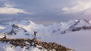 Successful Man Hiker On Top Of Mountain Peak Sunset Aerial Flight Over Cross Snowy Mountain Range