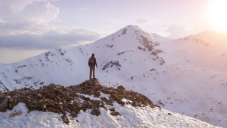 Young Hiker Reaching The Top Outstretched Arms Success Pose At Sunset In Snowy Mountain Range Aerial Flight Epic Victory Life Gratefulness Religion Concept
