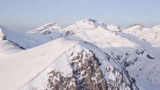 Aerial Flight Spinning Around Mountain Peak Epic Inspirational Flyover Winter Landscape