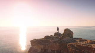 Young Man On Sea Vacation Standing On Edge Of Ocean Cliffs Enjoying Sunrise Happiness Nature Beauty Concept