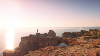 Young Man On Vacation Ocean Cliffs Raising Arms At Sunset Freedom Concept Aerial Footage