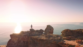 Man Raising Hands In Worship Pose At Top Of Ocean Cliff Rocks Sunrise Religious Faith Christianity Concept Aerial Shot