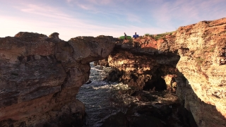Young Surfers Walking On Edge Of Sea Rocks Cliffs Aerial Vacation Happiness Holiday Concept