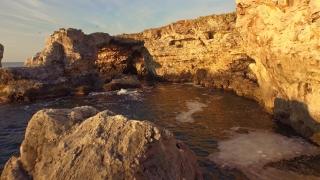 Aerial Fly Under Sea Rocks Beautiful Ocean Cliffs Cave Blue Water Sunrise Golden Light Scenic Beauty Sunshine Summer Vacation Concept
