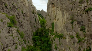 Epic Extreme Aerial Fly Through Mountain Cliffs Crack Split Between Rocks Revealing Beautiful Landscape Mountain Range Rock Formations Hiking Adventure Mountaineering Summer Spring Nature Beauty