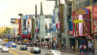 LOS ANGELES, USA - CIRCA JULY 2016: Tourists walk on Hollywood Boulevard while ads glow over them.